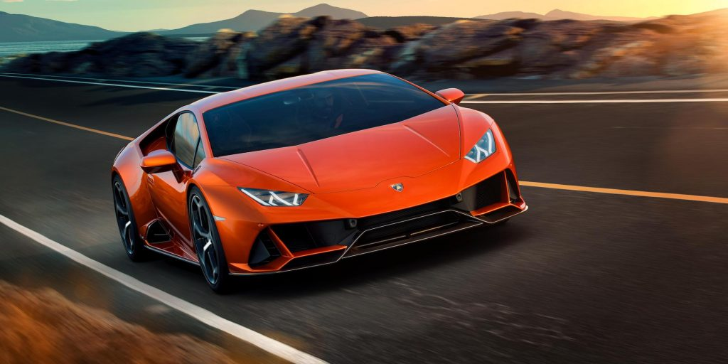An orange Lamborghini Huracán EVO travels on a paved mountain road