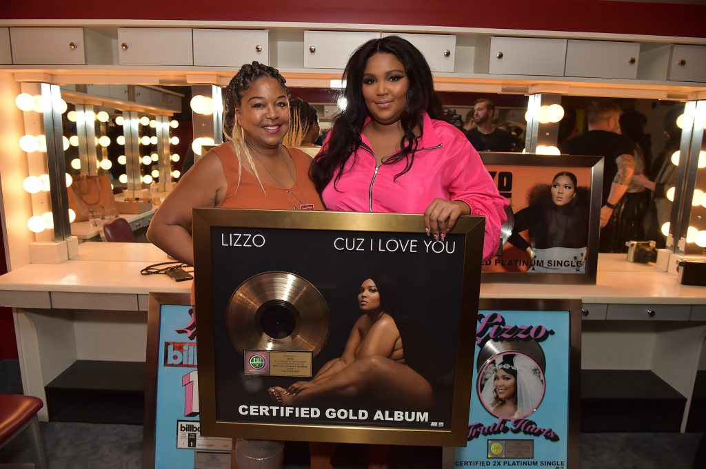 Lizzo and her mom smile proudly next to a plaque