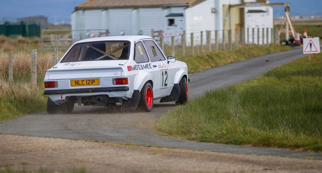 The rear view of a white MST Mk2 Ford Escort Group-4 Rally sliding around a corner