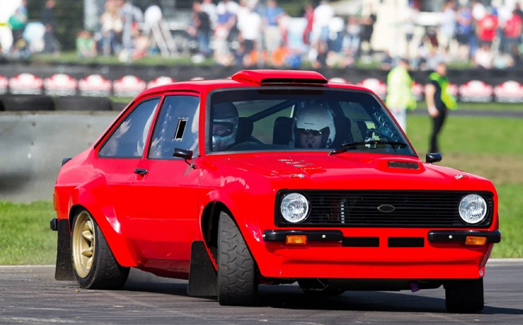 A red MST Mk2 Ford Escort Ultimate Rally Car drifts around a racetrack