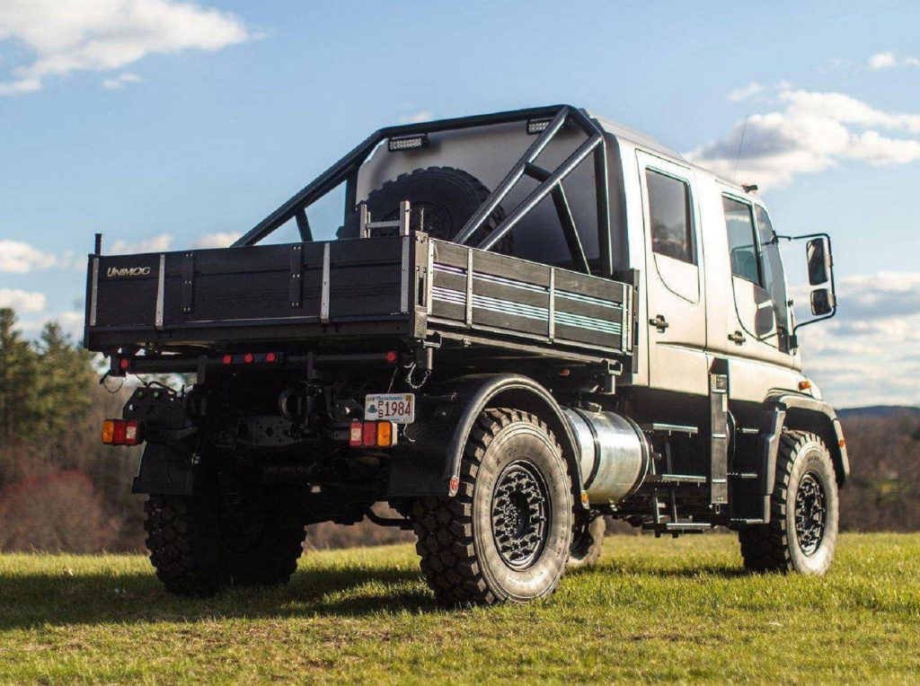 The rear 3/4 view of a modified silver 2004 Mercedes Unimog U500