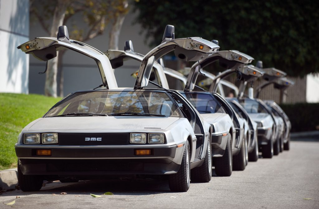 DeLorean are parked in a row and all have their gullwing doors open.