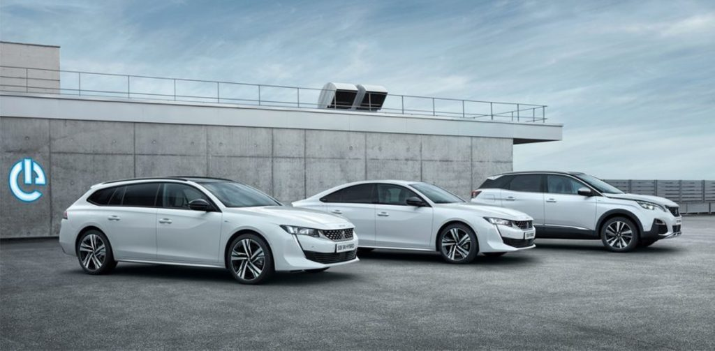 Three white Peugeot plug-in hybrid models are parked next to each other.