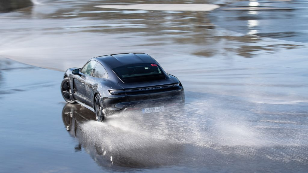 A black Porsche Taycan drifts on wet pavement