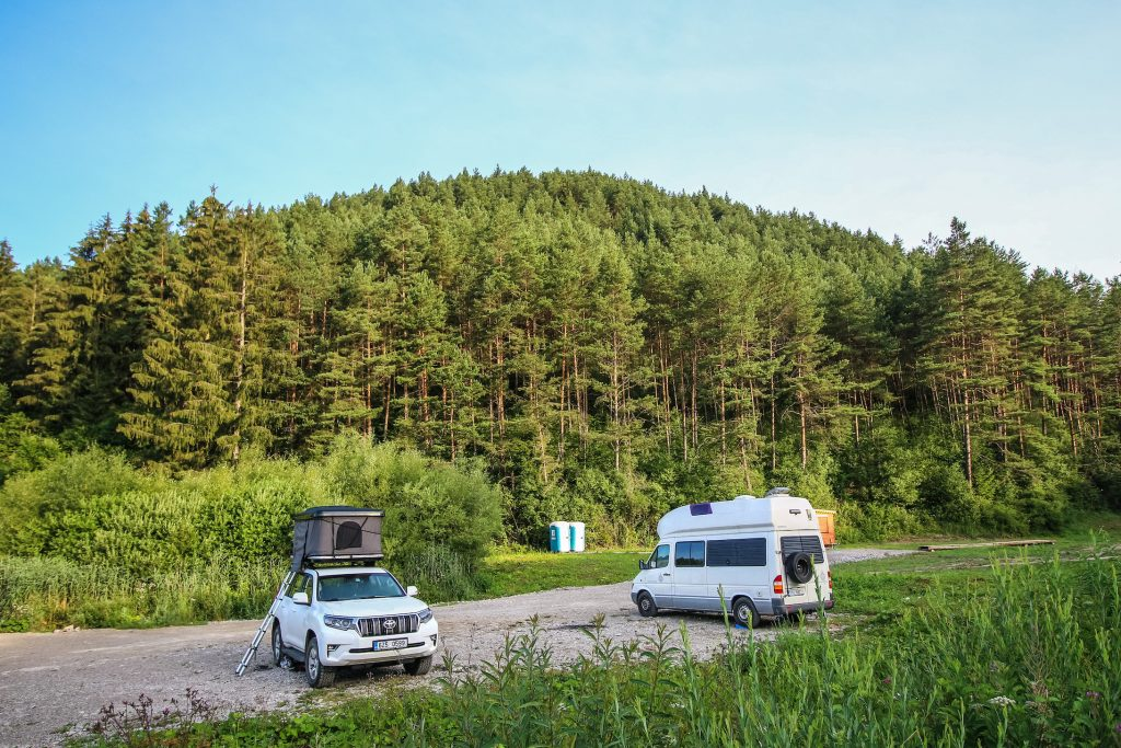 People camping in a 4x4 Toyota Landcriuser with a roof tent and Mercedes Sprinter James Cook edition RV camper van near the thermal lake Kalameny