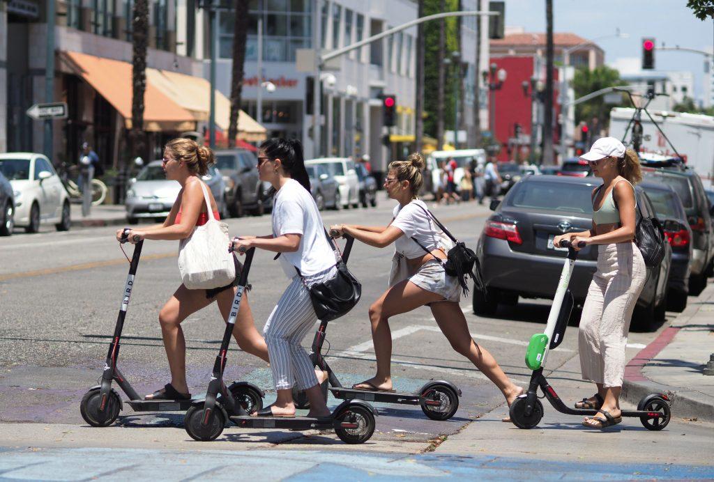 Women ride electric scooters in Santa Monica, California.