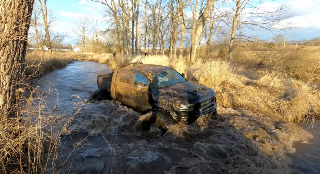 An image of a broken 2021 Ram 1500 TRX on enormous tires off-road.