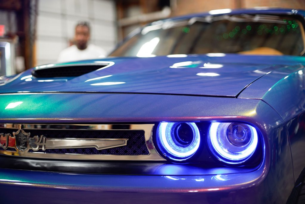 The grille of a modified violet 2017 Dodge Challenger with blue LED headlights