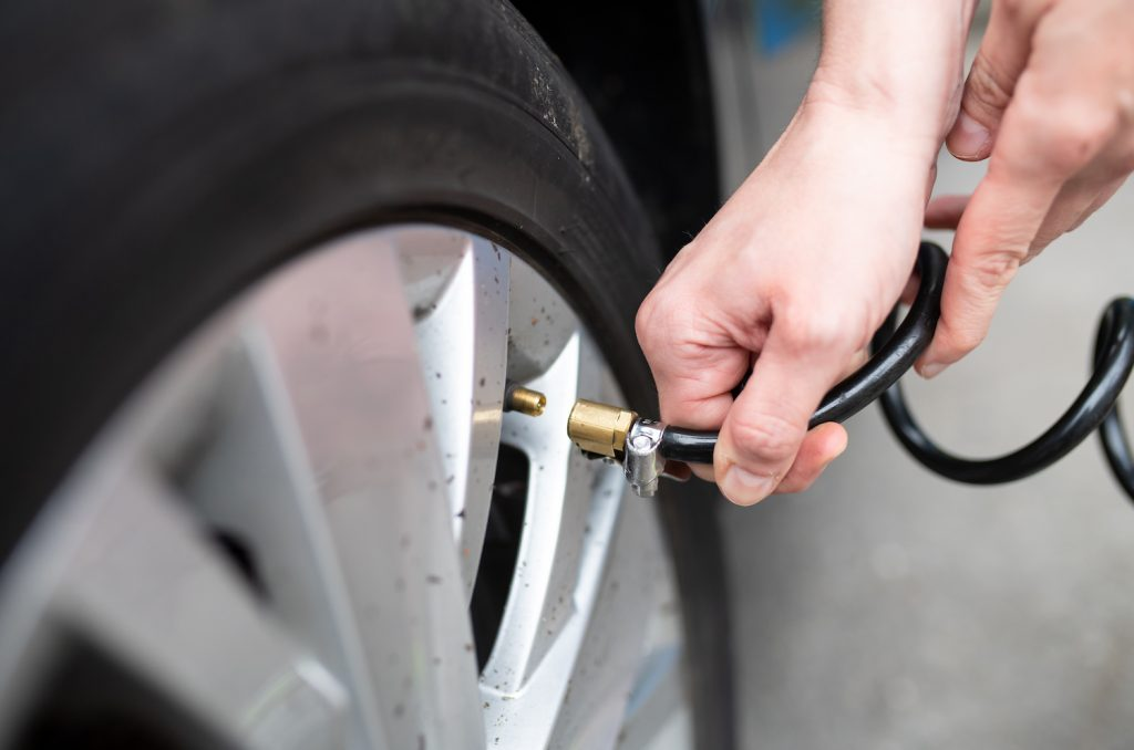 A woman checking her car's tire pressure