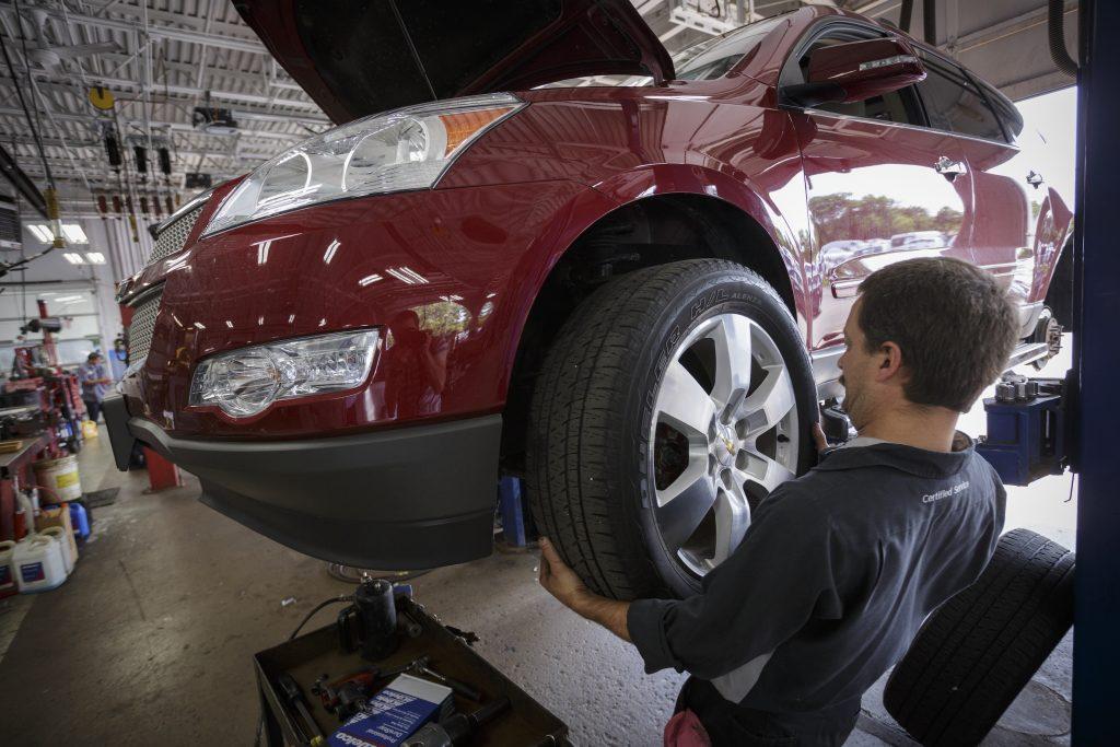 Technician Dave Serdar rotates the tires on a Chevy Traverse