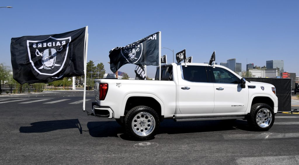Las Vegas Raiders fans drive in a pickup truck adorned with team flags as they arrive at a parking lot at Allegiant Stadium set up for socially distanced tailgating before the NFL game between the Buffalo Bills and the Raiders
