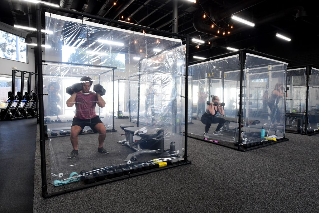 Car safety and Mental or physical health go hand in hand  People exercise at Inspire South Bay Fitness behind plastic in their workout pods