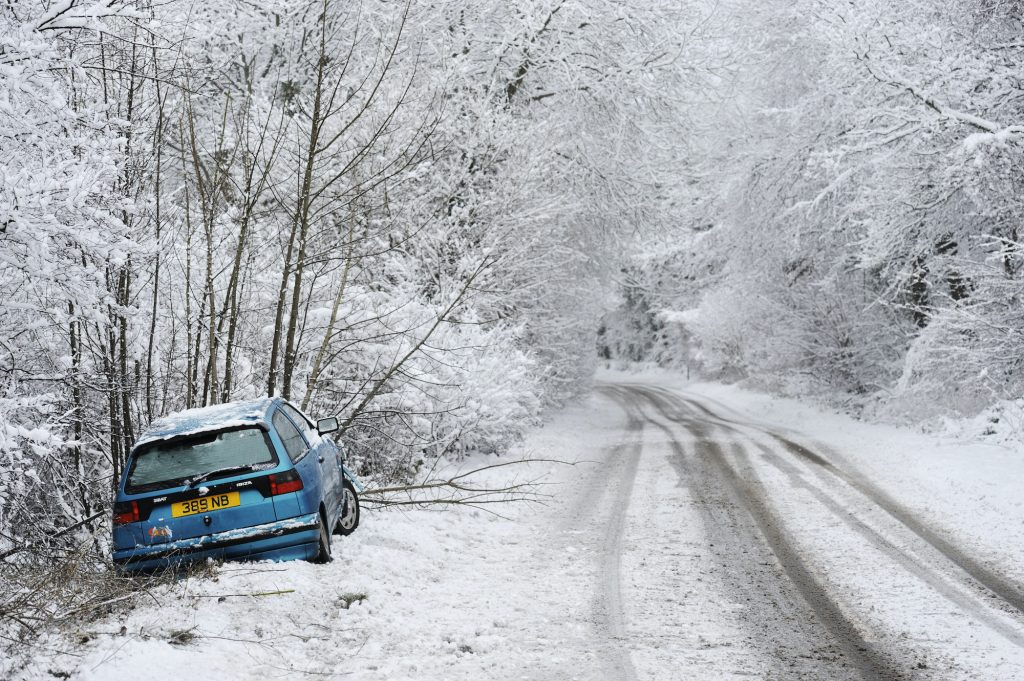 Abandoned car by side of road in snowy weather