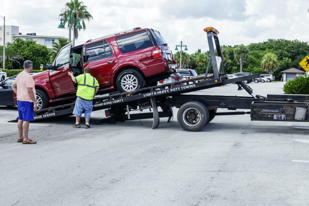 An SUV gets towed away on a tow truck