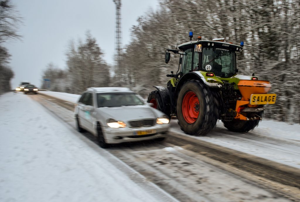tractor clears snow and spreads salt on a snowy road