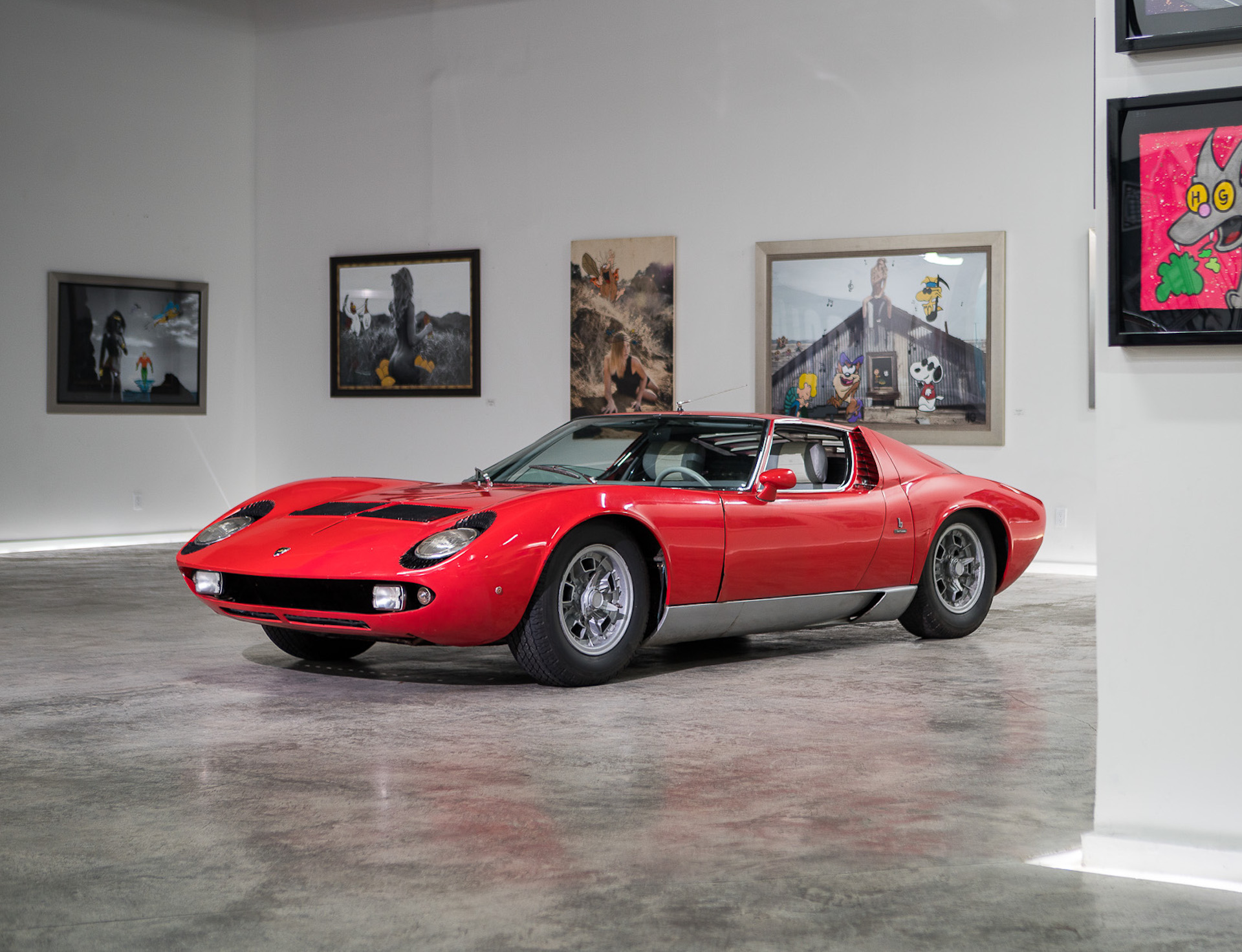 a red lamborghini Miura S parked in a gallery on display