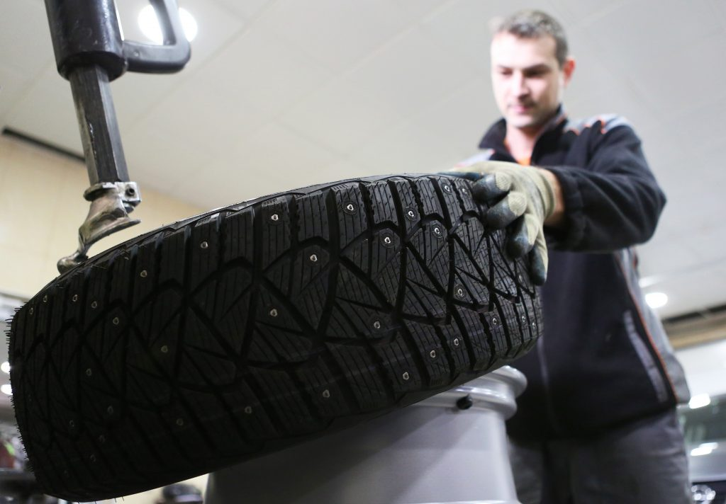 technician mounting studded tires