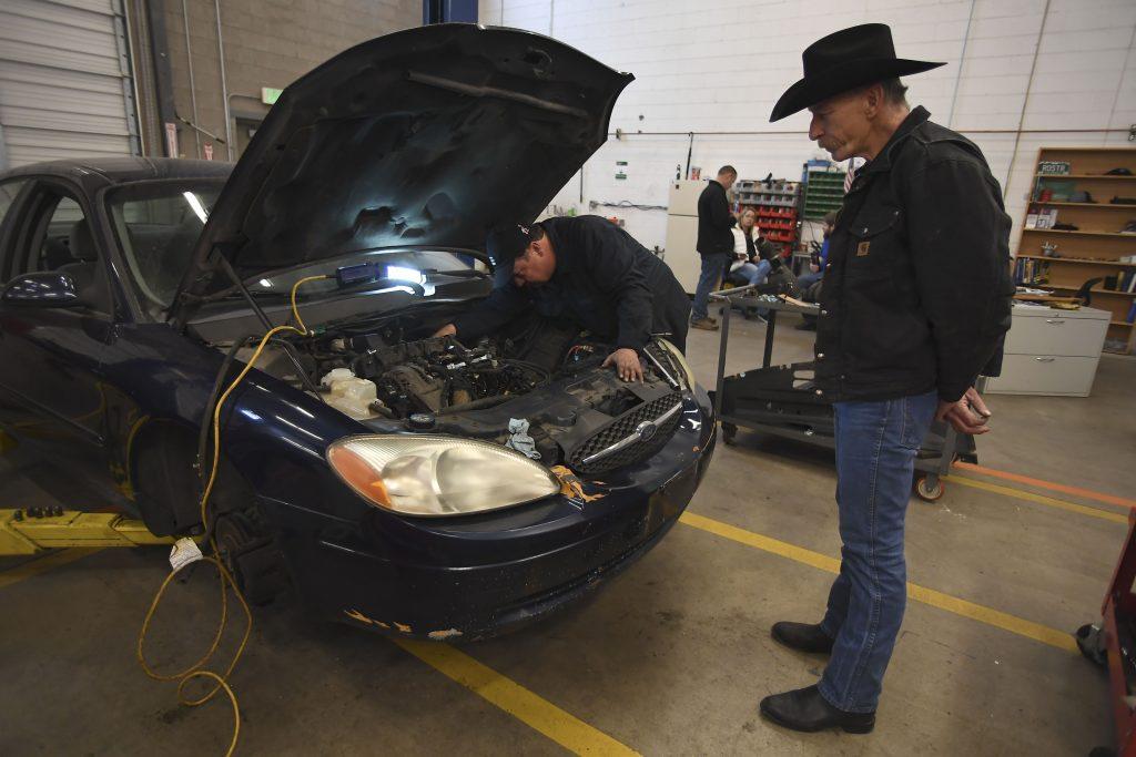 man watches mechanic work on car