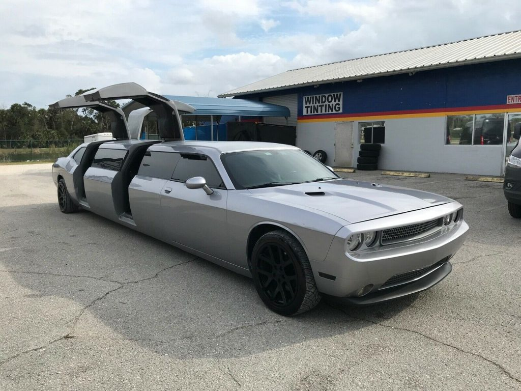 An image of a Dodge Challenger limousine outside with its doors open.