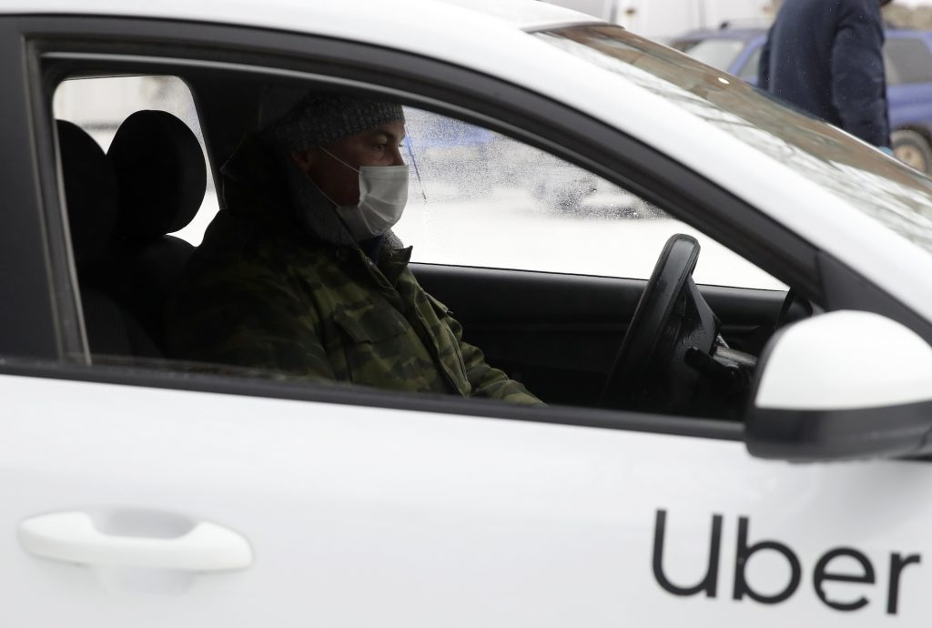 A taxi driver wears a protective mask in a car amid the COVID-19 pandemic
