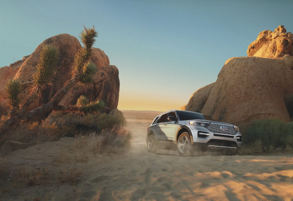 A silver 2021 Ford Explorer driving between two boulders on a sand pathway