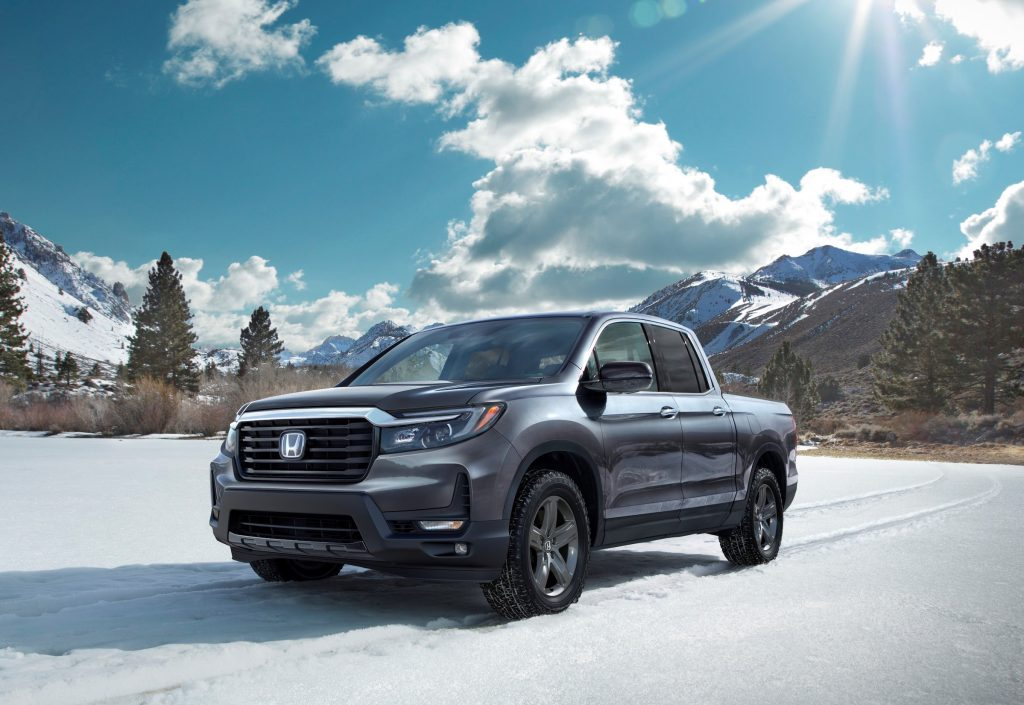 The 2021 Honda Ridgeline RTL-E parked in an open plain in front of trees.