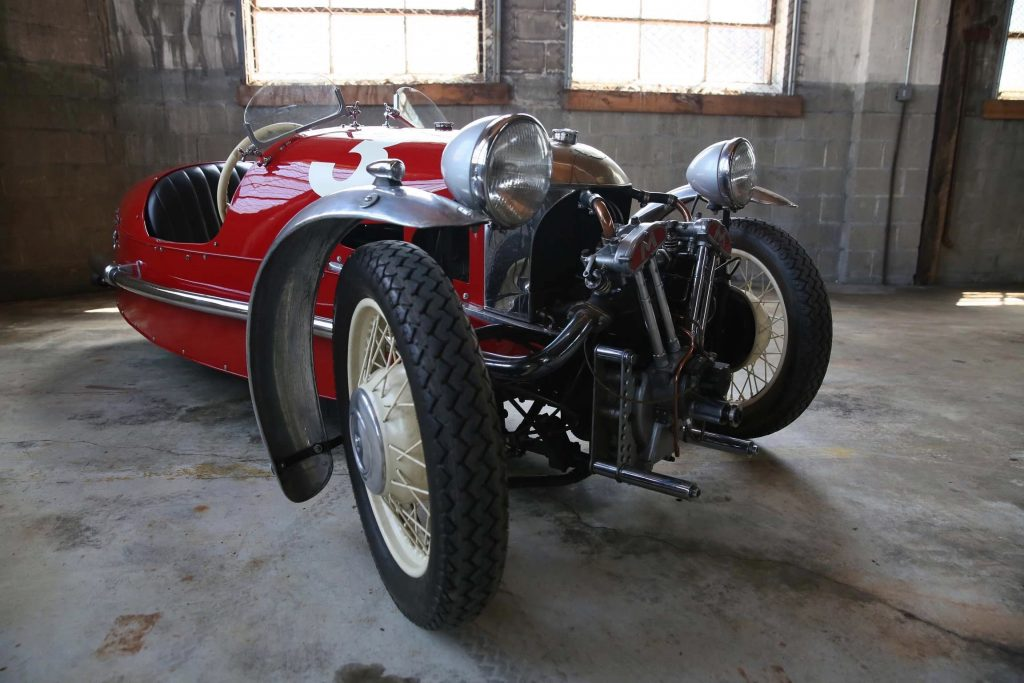 The front 3/4 view of a red 1933 Morgan 3-Wheeler Super Sport with a Matchless V-twin in a concrete garage