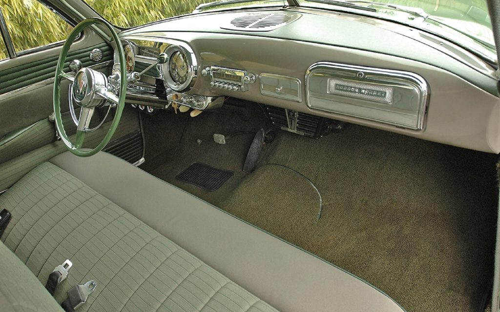 The green-and-tan front bench seat and dashboard of a 1952 Hudson Hornet Twin-H Power