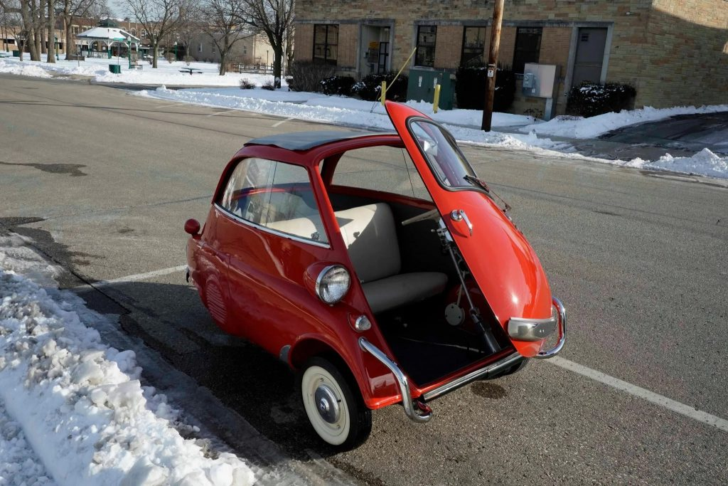 A red 1958 BMW Isetta 300 parked on a snowy city street with its door open