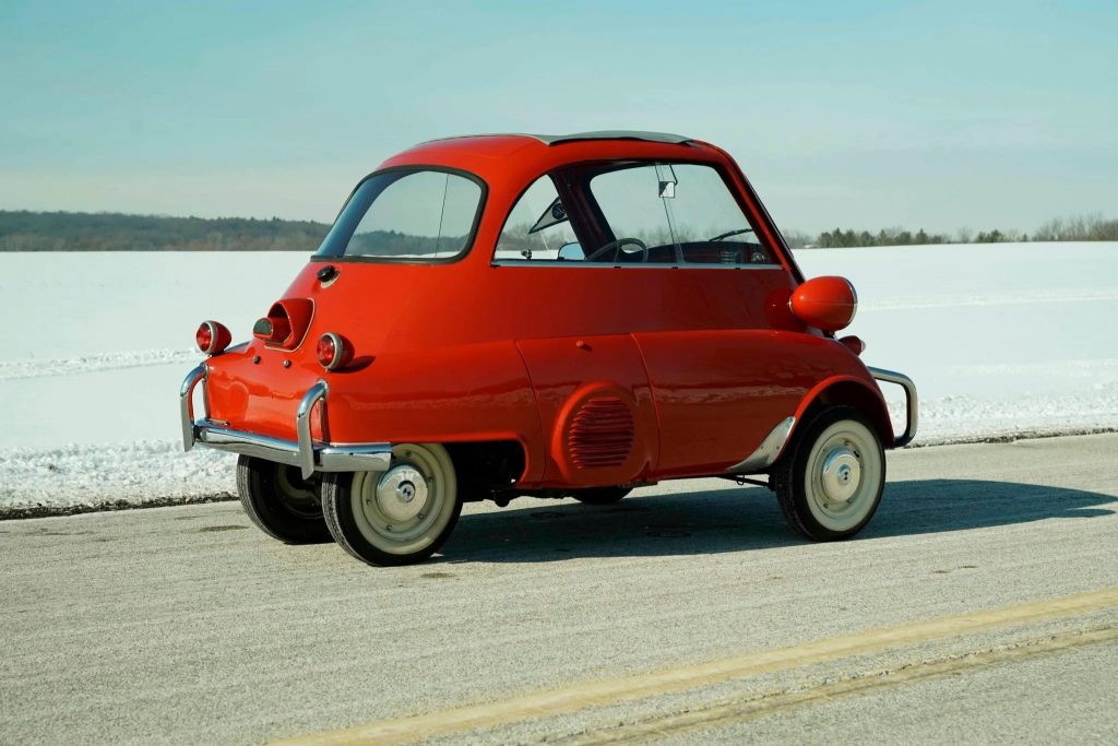 The rear 3/4 view of a red 1958 BMW Isetta 300 parked by a snow-covered field