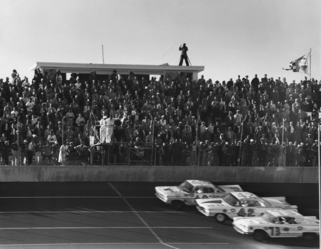 Three NASCAR cars, including Lee Petty's No. 42 Oldsmobile Super 88, head toward the finish line at the first Daytona 500 in 1959