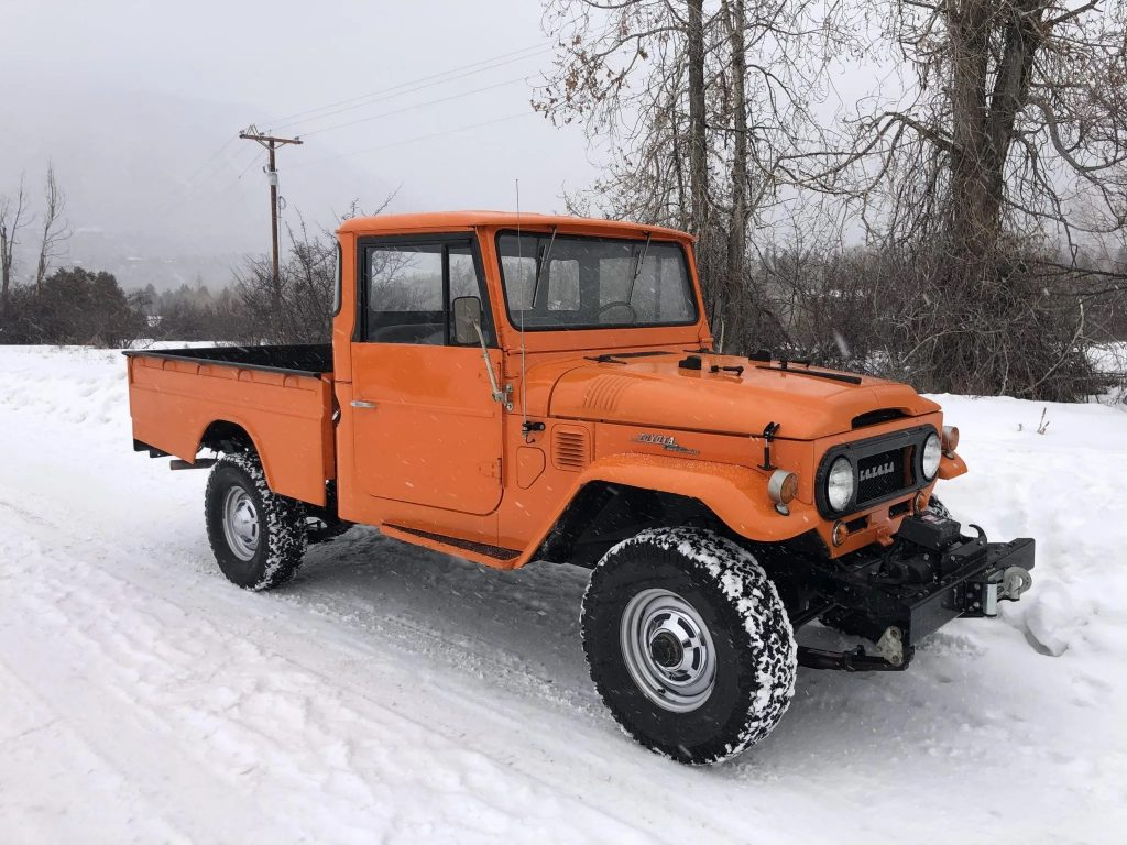 The front 3/4 view of an orange 1964 FJ45 Toyota Land Cruiser pickup in the snow
