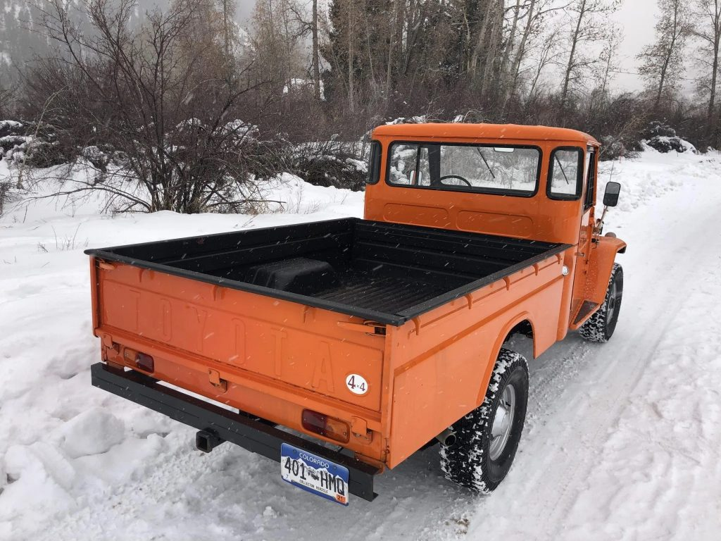 The rear 3/4 view of an orange 1964 FJ45 Toyota Land Cruiser pickup on a snowy road