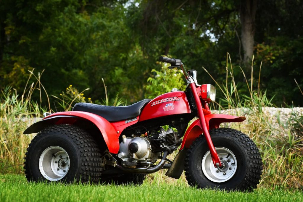 The side view of a red 3-wheeled 1979 Honda ATC 110 in a field