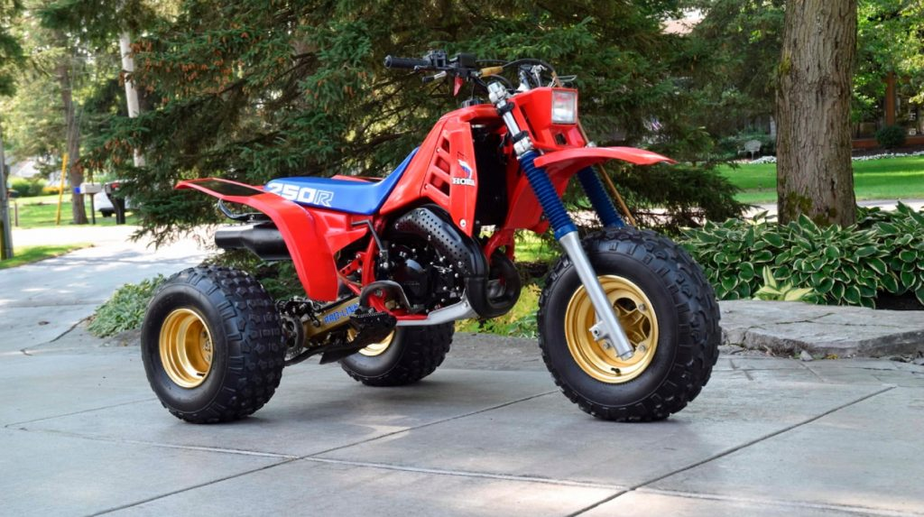 A red 1985 Honda ATC 250R with a blue seat on a driveway