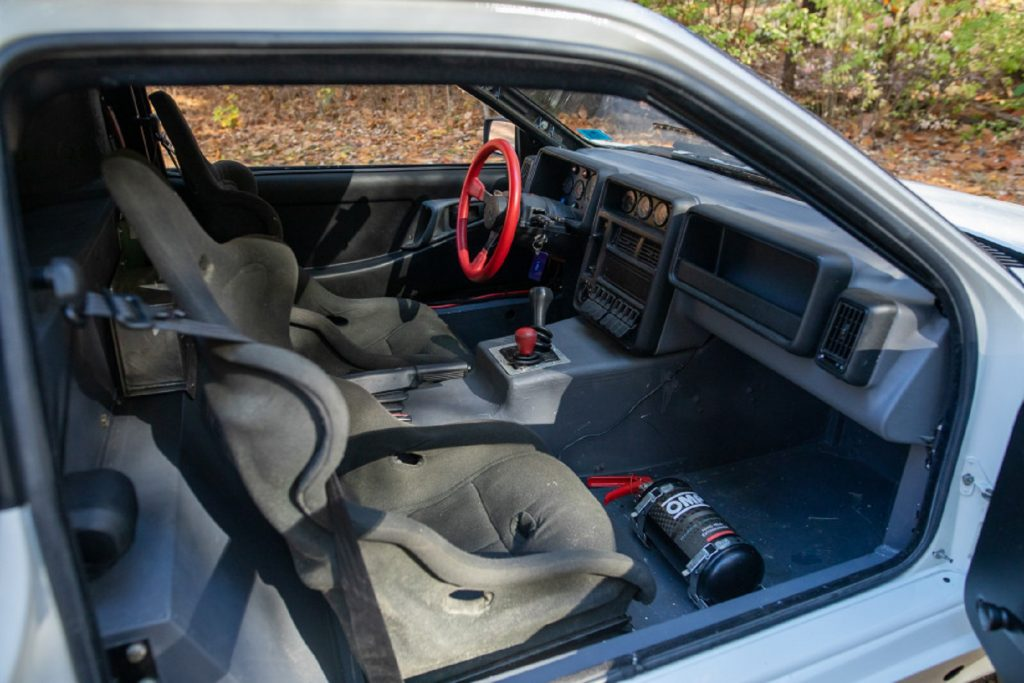 The Sparco seats, red steering wheel, and dashboard of a 1986 Ford RS200 Evolution