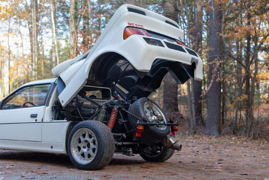 The rear of a white 1986 Ford RS200 Evolution in the forest with its rear winged section raised showing its chassis and engine