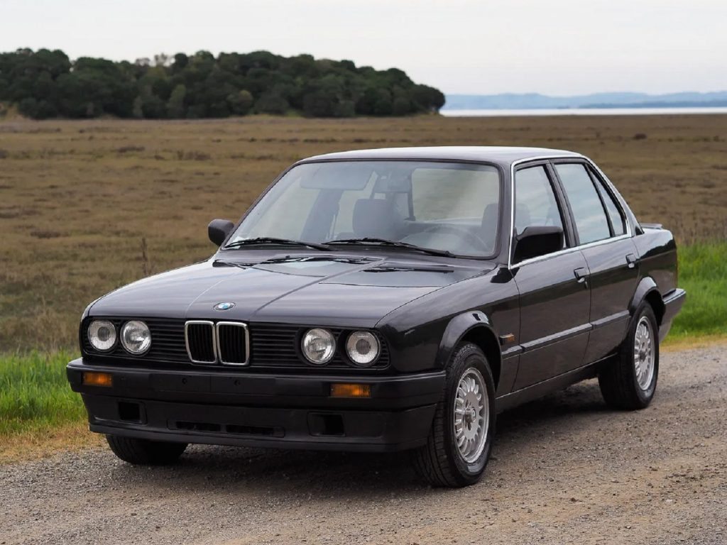 A black 1988 BMW 320is by a field