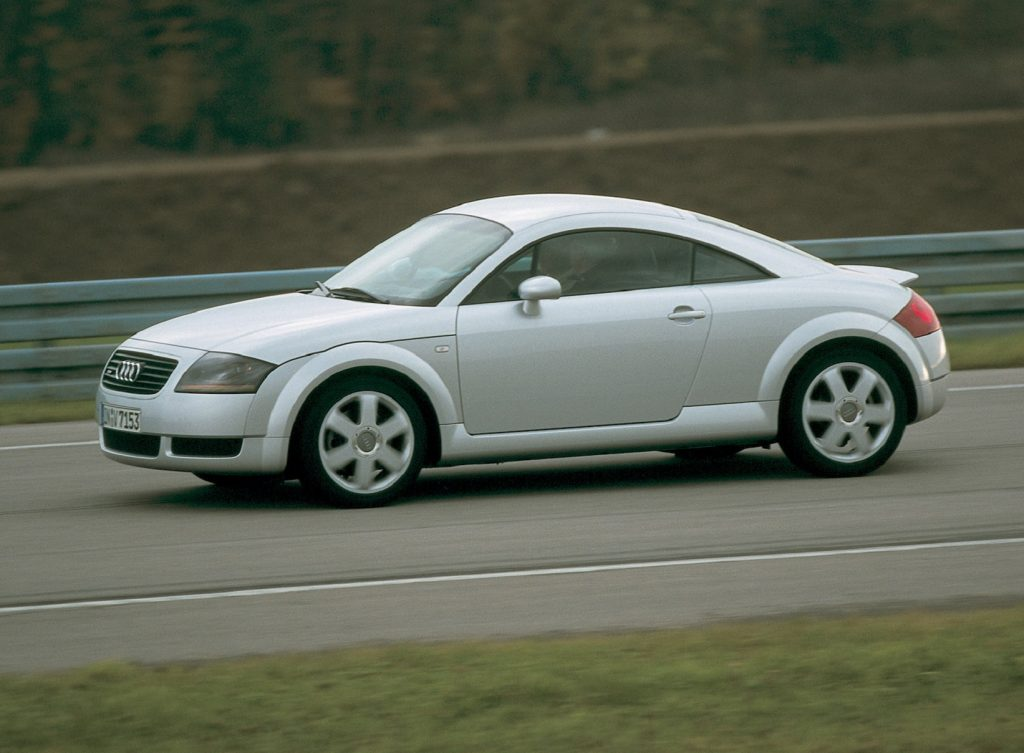 The side view of a silver 1999 Audi TT Coupe on a track