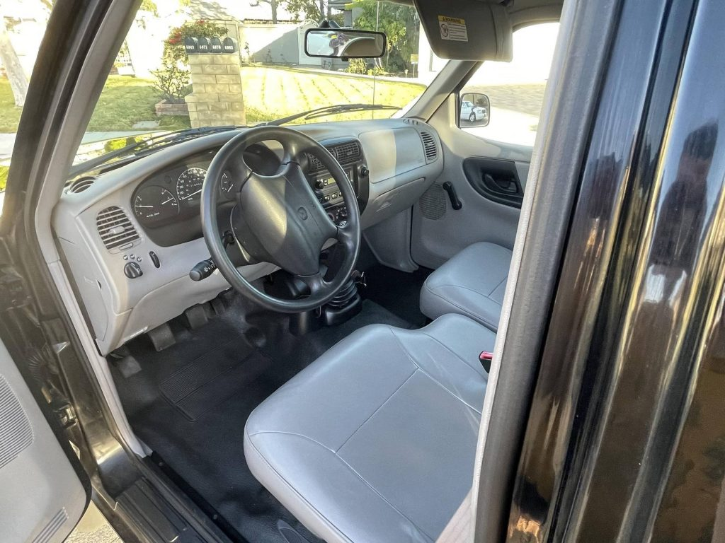 The grey bench seat and dashboard of a 2000 Mazda B3000 SX