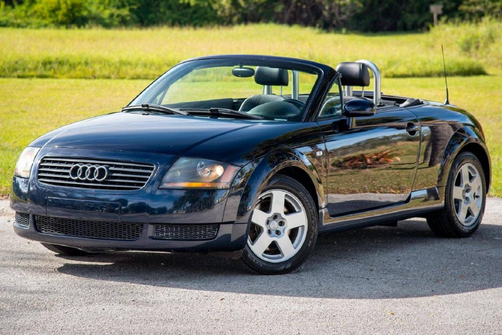 A black 2002 Audi TT Roadster with its roof down