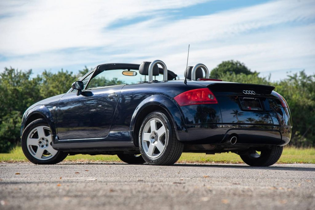 A low-angle rear 3/4 view of a black 2002 Audi TT Roadster with its top down and radio antenna up