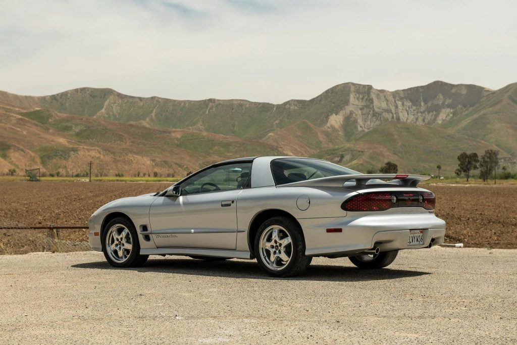 The rear 3/4 view of a silver 2002 Pontiac Firebird Trans Am WS6 on a dirt parking lot by a mountain range