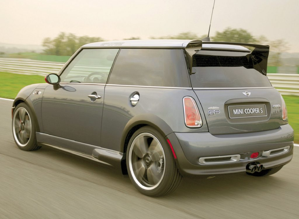 The rear 3/4 view of a gray 2006 Mini Cooper S John Cooper Works GP driving on a racetrack
