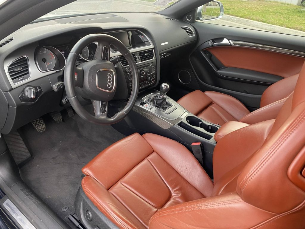 The brown-leather front seats and black dashboard of a 2009 Audi S5 Coupe
