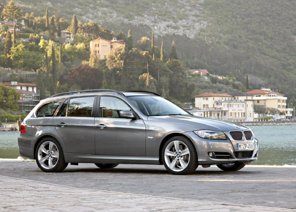 A gray 2009 E91 BMW 3 Series Wagon parked by an lake among green rocky hills
