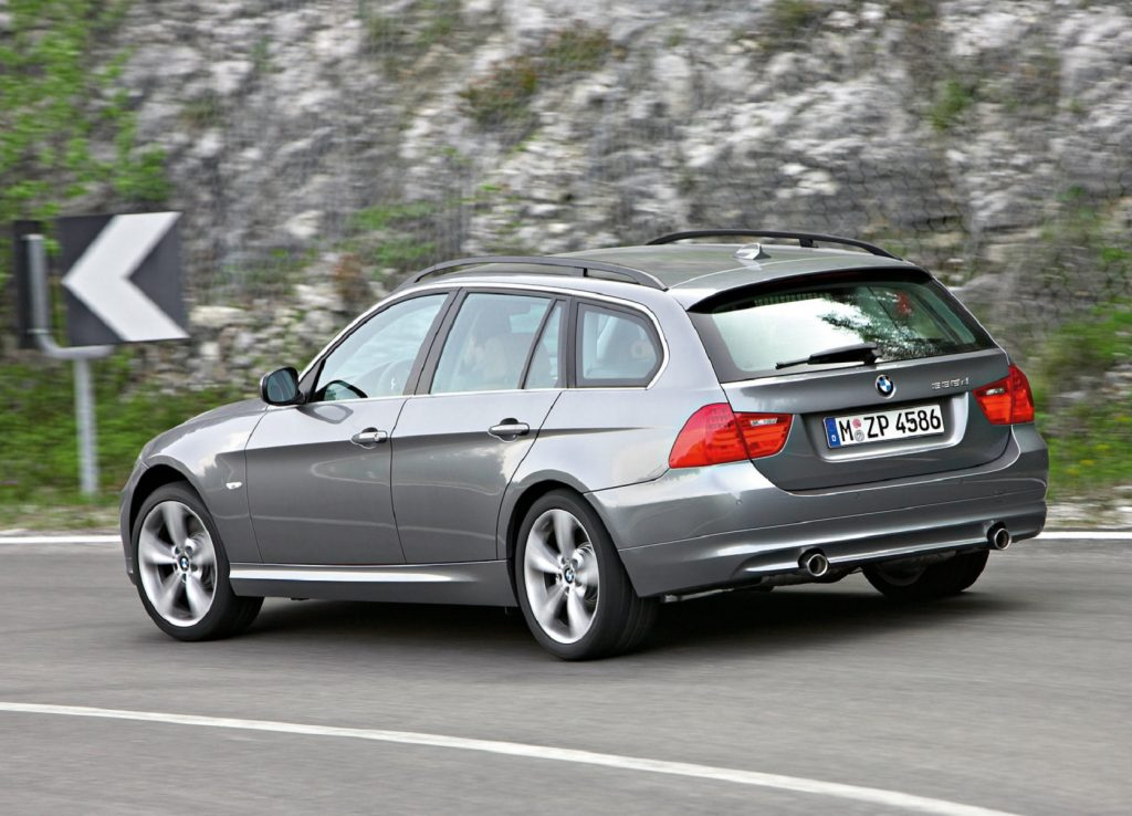 The rear 3/4 view of a gray 2009 E91 BMW 335d Wagon driving around a mountain road corner