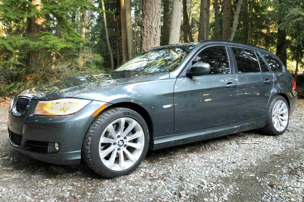 A dark-green 2011 BMW 328i Sports Wagon on a forest gravel path