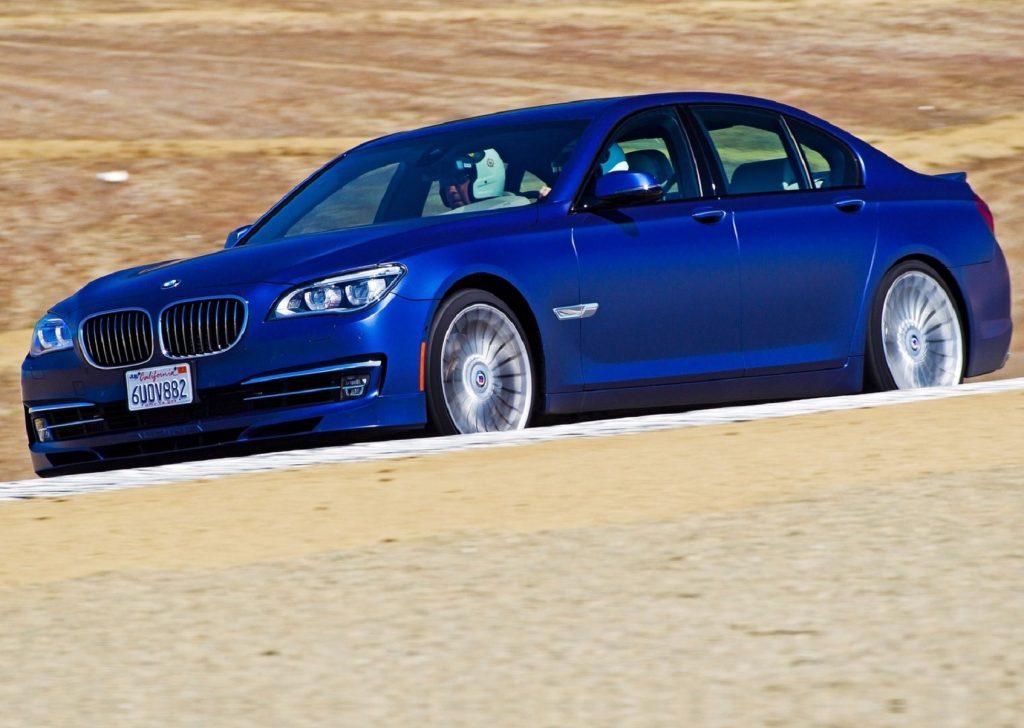 A bright-blue 2013 BMW Alpina B7 drives around a desert racetrack