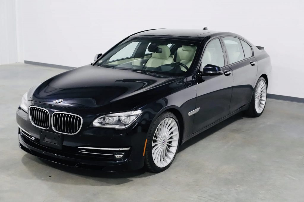 A dark-blue 2013 BMW Alpina B7 xDrive in a white warehouse